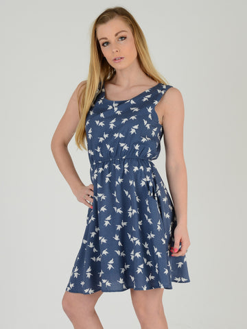 Our Model wears this sleevless blue dress with a bird print.