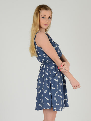 Our Model wears this sleevless blue dress with a bird print. She is 5ft 5 inches tall and wears an size UK 8, this picture is taken from the side with her looking over her shoulder