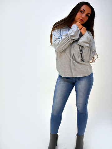 a full length shot of our long sleeve grey top with bell sleeves paired here with light blue jeans