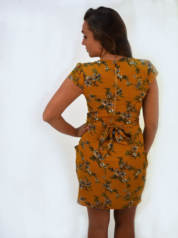 A back picture with our mustard floral dress, with the model with 1 arm out in a posed photo.