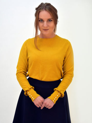 A picture of our model wearing a mustard jumper with stylish detail in the sleeve with pearls and frills at the end. Here tucked into a navy skater skirt