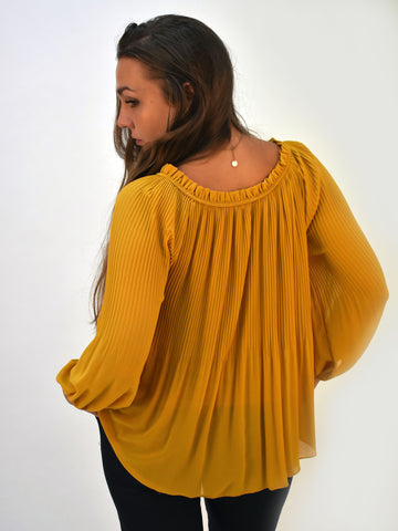 A back picture of our mustard pleated blouse with our model looking over her shoulder