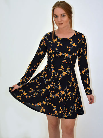 A picture of our navy floral long sleeve dress. This image is been taken from the front , can be worn bare legged or with navy tights