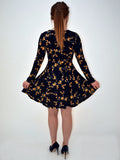a picture of our model wearing our navy floral long sleeve dress. In this image from the back the model shows off the shape of the dress