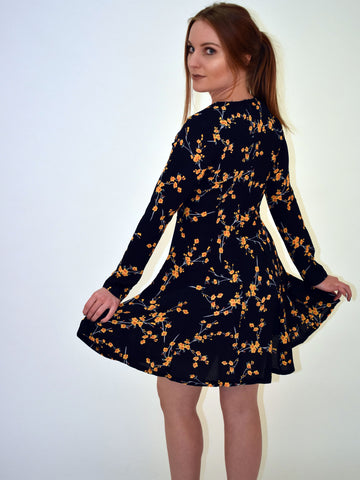A side on image with our model looking over her shoulder. This navy floral long sleeve dress with mustard flowers is a must have.