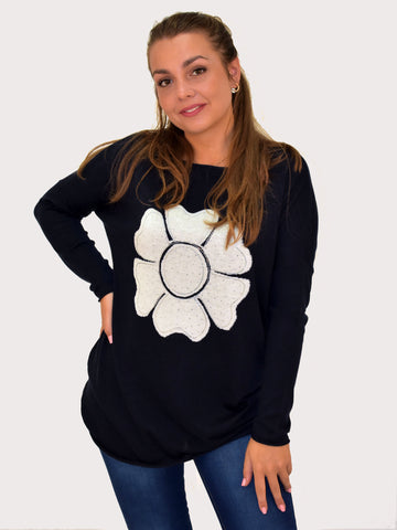 A front on picture of our model wearing a navy jumper with a white flower with diamantes.