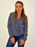 A front on picture of our model wearing a crossover navy blouse long sleeve with a white pinstripe.