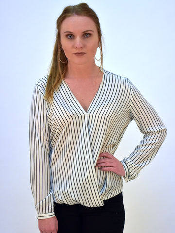 Model wearing a white cross over blouse with a black stripe. This picture is taken from the front