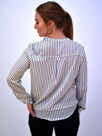 Model wearing a white cross over blouse with a black stripe this picture is taken from the back