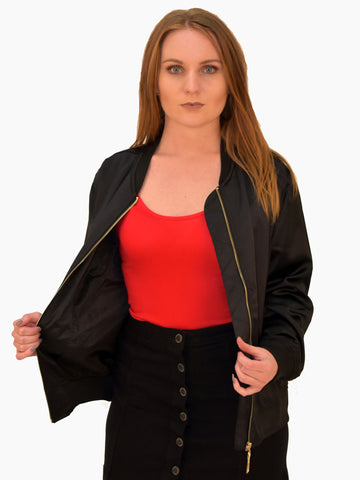 A picture of our black bomber jacket, simple but ever so effective for autumn. In this picture paired with our red bodysuit and black denim skirt.