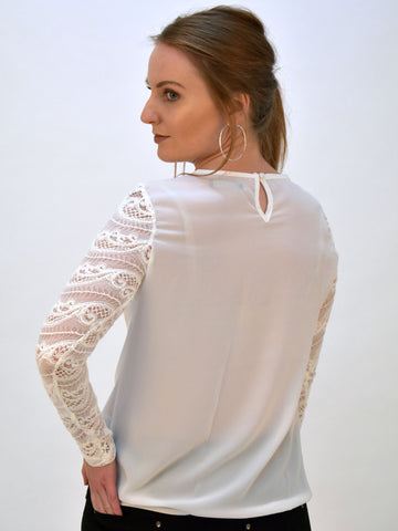 A back picture of our long lace sleeve blouse in Ivory. The detasiling on the sleeve makes for an elegant product, our model has her head looking over her shoulder.