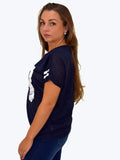 A side picture of our navy print tshirt that has 98 on the front. our model is 5ft 5 inches tall and wears an uk size 8 or 10