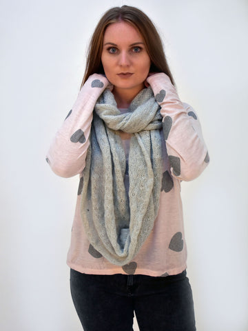 a picture of our long sleeve top in pink with silver hearts on. This picture is taken from the front and shows the model with a grey snood to finish off the look.