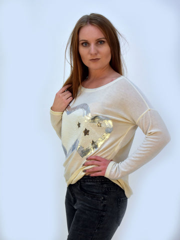 Picture of our model wearing our cream super soft jumper with a heart print on the front.
