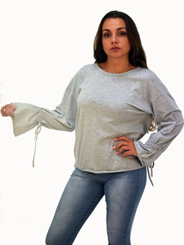 A picture of our model wearing our grey long sleeve top, this picture shows the bell sleeve detail.