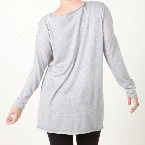 A back picture of our model who is wearing a light grey jumper with a diamante flower in white.