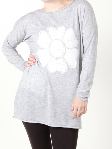 A front on picture of our model who is wearing a light grey jumper with a diamante flower in white
