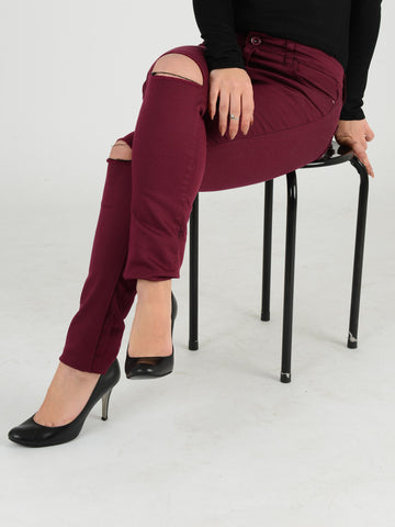 Close up of our Burgundy skinny jeans with our model sitting down . Our Model is 5ft 3 and wears a UK size 8