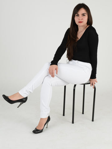 A  full length close up Photo of our white skinny jeans of our model sitting on a stool .