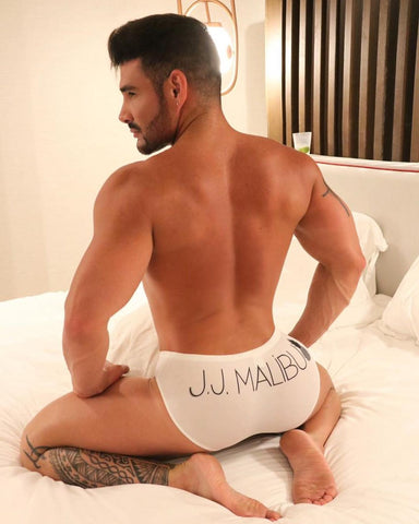 Latino man sitting on a white bed facing away from the camera wearing white briefs with JJ Malibu label on his bum