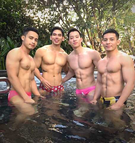 Group of muscular asian men standing in pool wearing JJMalibu speedos