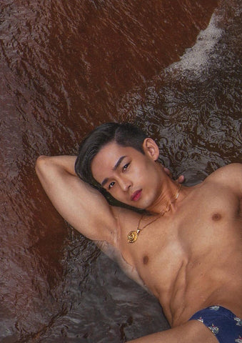 Asian man laying on a wet brick red rock in shallow water looking up at camera with a neat quiff in his hair