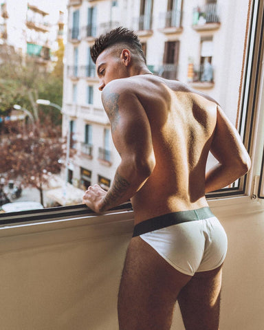 Man looking out window wearing only white JJ Malibu briefs