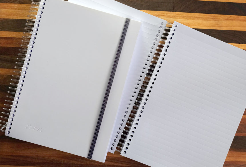 Image of two spiral notebooks on a table from above. Both white, bottom notebook open