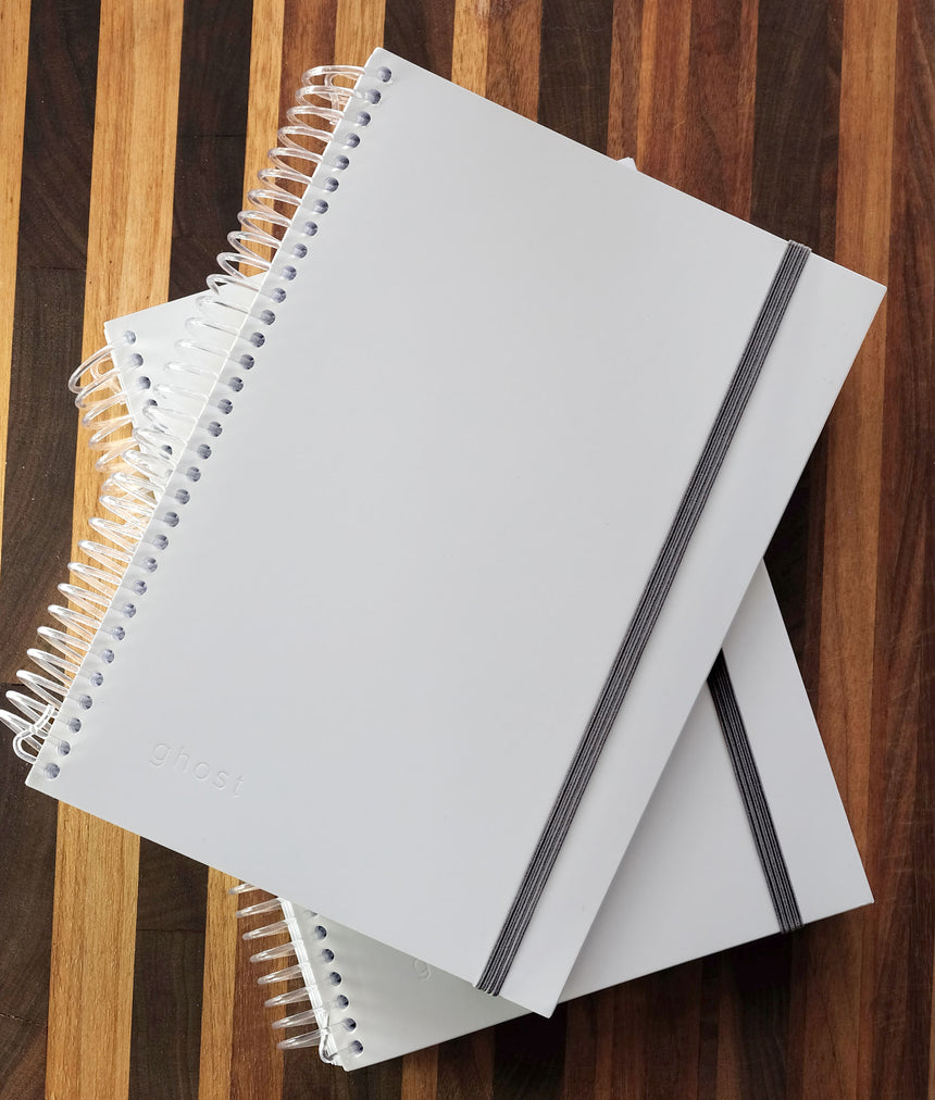Two closed ghost paper spiral notebooks stacked on top of one another