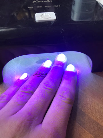 Glowing gel nails under the lamp