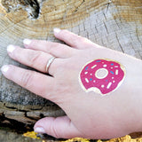 Small donut tattoo on woman's hand | Photo by Jewel Flash Tattoos
