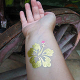 Hawaii flower temporary tattoos Gold Hibiscus stickers | Photo by Jewel Flash Tattoos