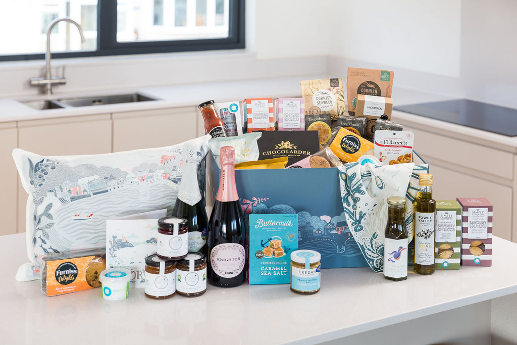 Cornish Food Hamper on kitchen counter with Cornish-illustrated box and Cornish food products including Cornish Larder, Freda's Peanut Butter and Cornish Sea Salt