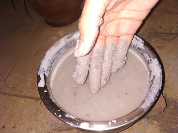 Mixing clay and coriander seeds