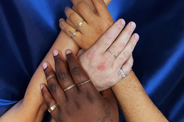 4 hands holding each other with rings