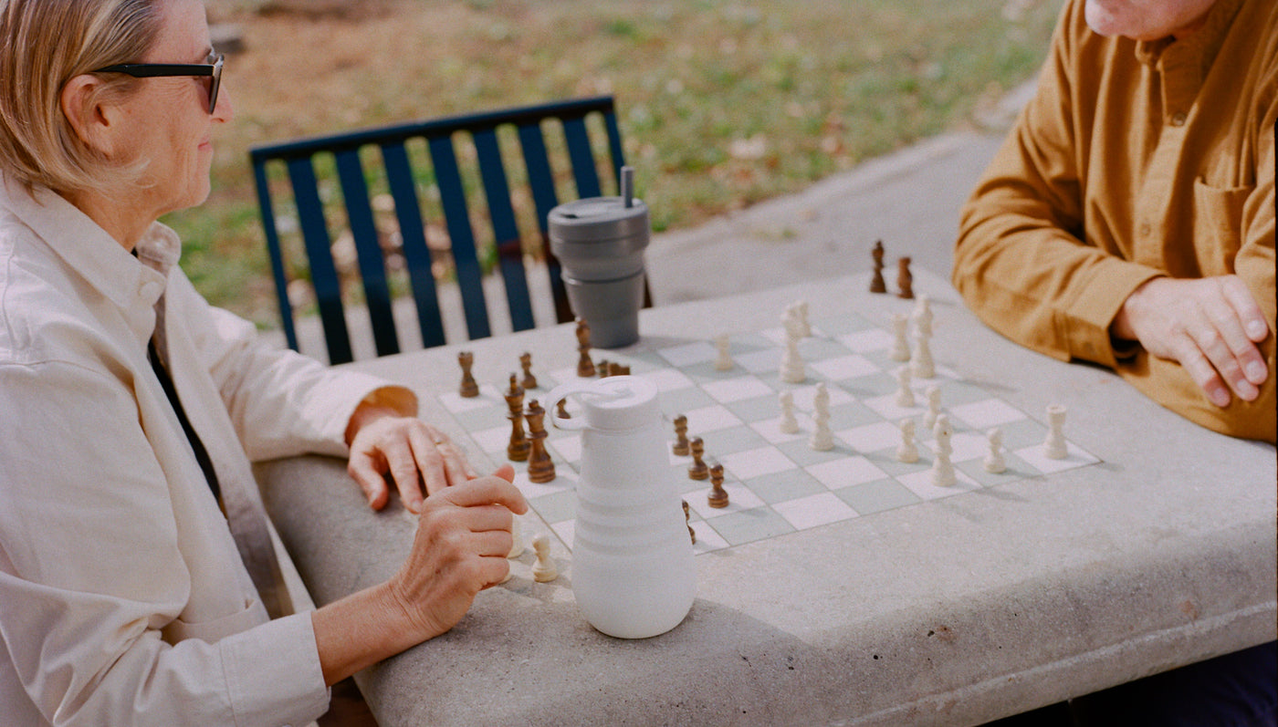 People in Park Playing Chess While Drinking from Stojo Products