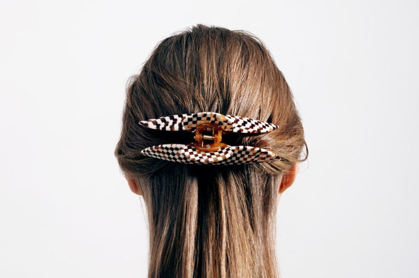 Back of woman's head with a brown wide hair clip