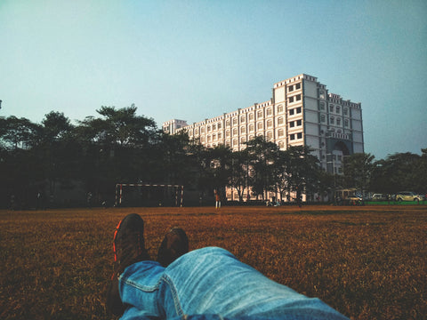 Person lying on a soccer field with a building in the background