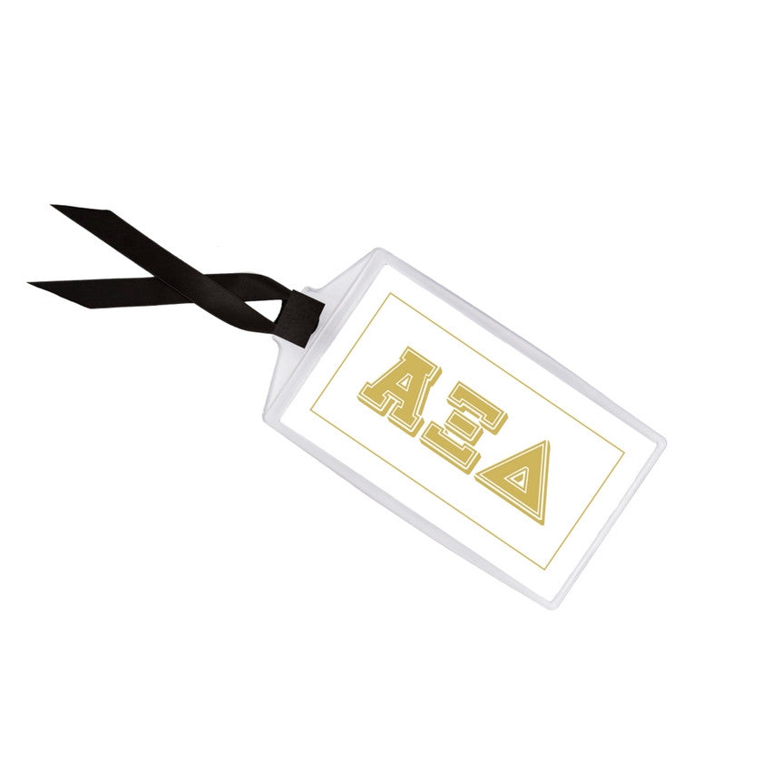 Alpha Xi Delta luggage tag measures 3.5 inches x 2 inches with black grosgrain ribbon.