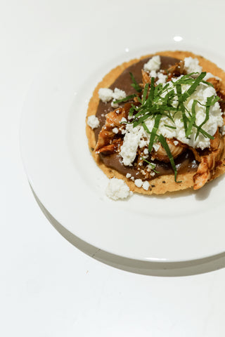 Tostadas de Tinga Poblana; mini homemade tostadas topped with refried pinto beans, chipotle stewed chicken, queso fresco crema and fresh epazote