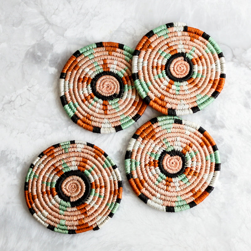 Dusty Peach Nyota Coasters made of sisal and sweet grass in orange, green and pink by Kazi Goods All Across Africa