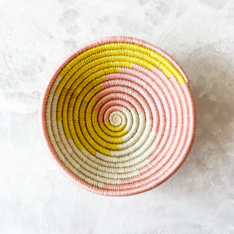 Small Blush Pink and Sun Unity Bowl made of sisal and sweet grass in pink and yellow by Kazi Goods All Across Africa