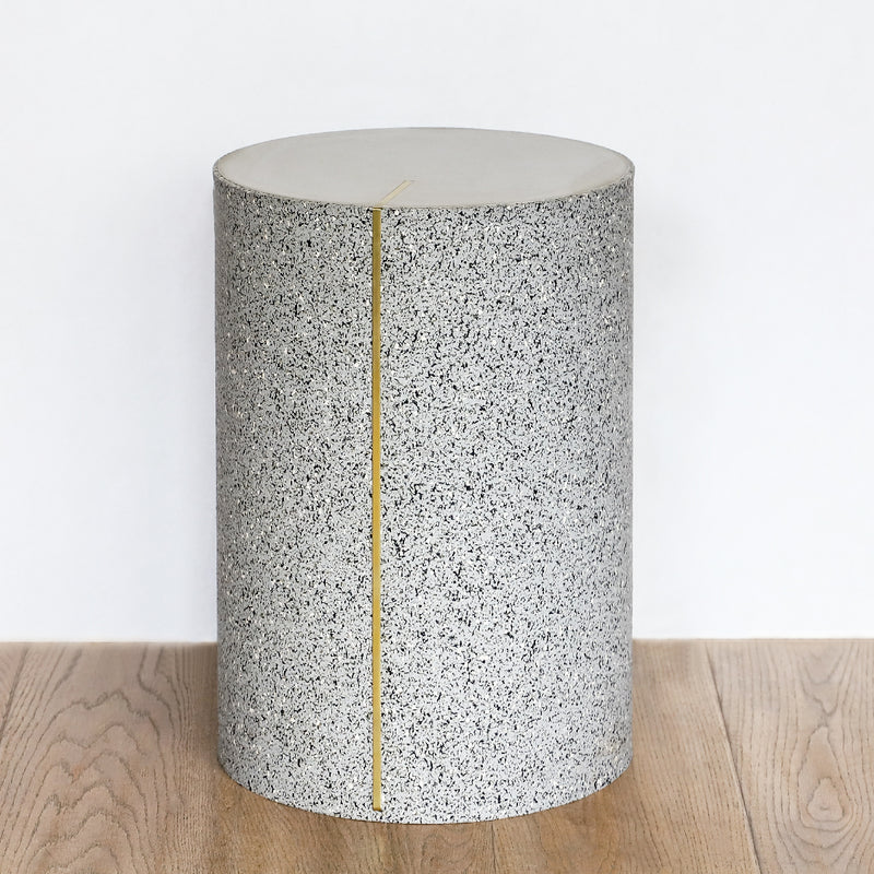Rubber Cylinder Side Table in gris gray with brass accents and a concrete top
