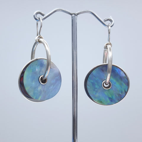 'Sputnik' earring design feature the concave-shaped inside of the shell. The New Zealand paua shell (haliotis iris) is from Stewart Island, Chatham Islands, or the Southland coastline, places where the seas are roughest and the shell is thickest. Pure silver reflector disc behind (more tarnish-resistance than sterling). Solid sterling silver hoops. Sterling silver earwires. Variations: Pearl shell from the Cook Islands, and New Zealand nephrite jade (pounamu) from New Zealand's South Island.