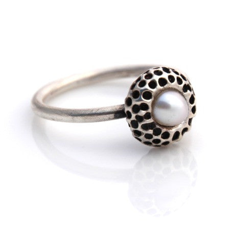 Stylized kina with freshwater pearl centre on a sterling silver rounded band.