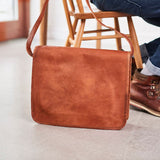 Medium size leather laptop messenger bag on floor