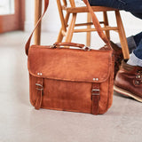 Leather laptop bag with handle in tan set on floor