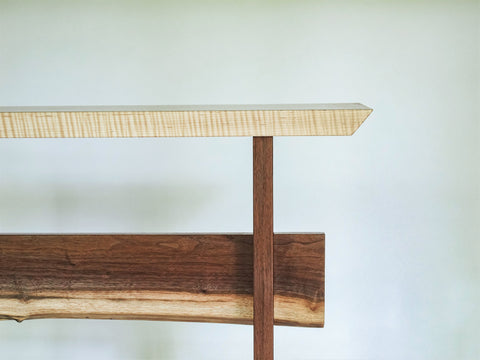 Our Statement Table is available with a live edge stretcher- pictured here with a tiger maple table top and walnut base