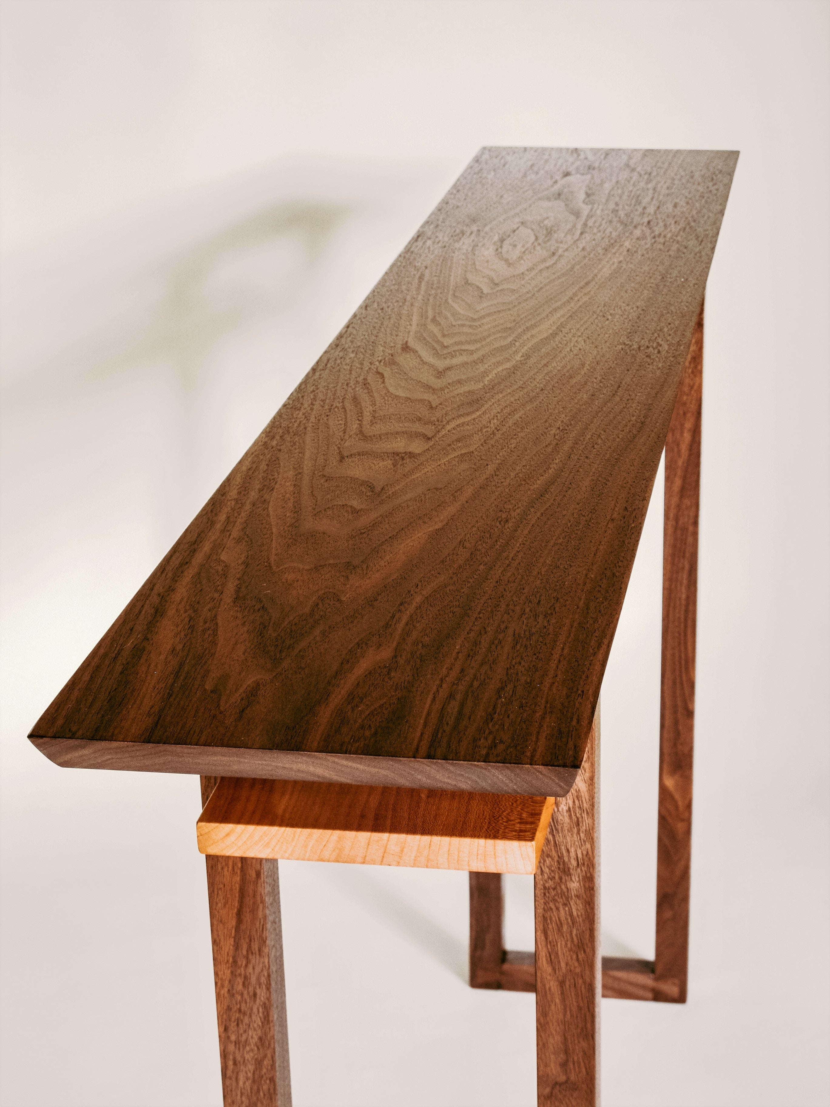 Premium solid woods of walnut and cherry create this narrow console table