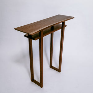 A narrow wooden table created from solid walnut with a live edge table top